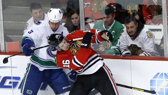 Vancouver Canucks defenseman Kevin Bieksa (3) pulls back on the stick of Chicago Blackhawks center Marcus Kruger, from Sweden, during the second period of an NHL hockey game Tuesday, Feb. 19, 2013 in Chicago. (AP Photo/Charles Rex Arbogast)