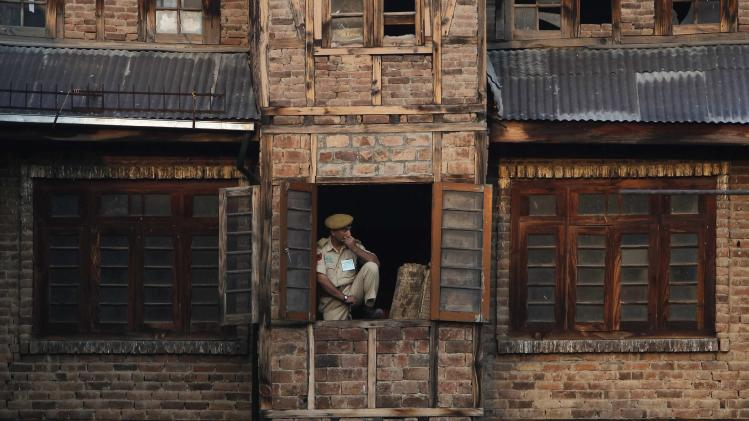 An Indian policeman keeps a vigil through the window of a residential building next to the Martyrs' graveyard, during Martyrs' Day in Srinagar