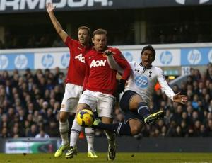 Tottenham Hotspur's Paulinho challenges Manchester United's Rooney during their English Premier League soccer match at White Hart Lane in London
