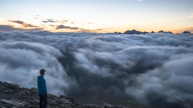 A tourist the sunrise above a sea of fog on Eggishorn mountain (2927 meters over sea level), in Fiesch, Switzerland, early Tuesday, July 28, 2015. (Dominic Steinmann/Keystone via AP)