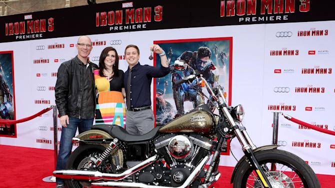 """IMAGE DISTRIBUTED FOR HARLEY DAVIDSON - Sean Threadgill, a Jackson, Tenn. firefighter, right, and his wife, Jenny, center, are presented the keys to a 2013 Harley-Davidson Dyna Street Bob motorcycle by Dino Bernacchi, right, Director of Marketing Communications at Harley-Davidson, on the red carpet at Marvel's Iron Man 3 premiere, on Wed., April, 24, 2013 in Los Angeles. Sean won the motorcycle as part of the """"Man & Machine"""" national promotion co-sponsored by Harley-Davidson and Marvel. (Photo by Casey Rodgers/Invision for Harley-Davidson/AP Images)"""