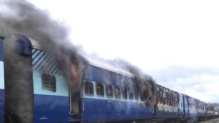 Coaches of the Rajya Rani Express train burn after a mob set it on fire as it ran over a group of Hindu pilgrims at a crowded station in Dhamara Ghat, Bihar state, India, Monday, Aug.19, 2013. At least 37 people were killed. (AP Photo)