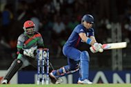 England cricketer Luke Wright (R) is watched by Afghan wicketkeeper Mohammad Shahzad as he plays a shot during their ICC Twenty20 Cricket World Cup match at the R. Premadasa Stadium in Colombo. Wright smashed an unbeaten 99 off 55 balls as defending champions England overcame a bad start to post 196-5 against Afghanistan