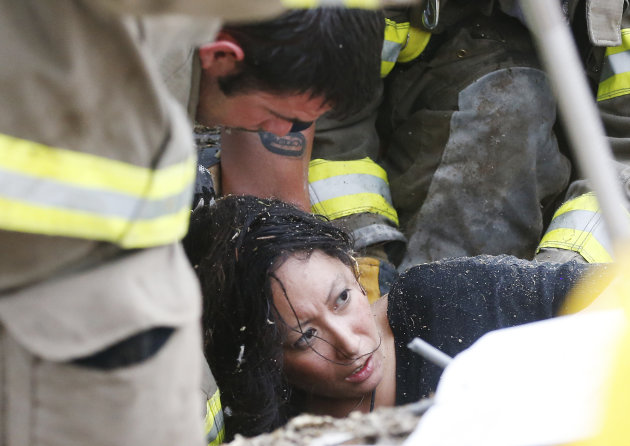A woman is pulled out from under tornado debris at the Plaza Towers School in Moore, Okla., Monday, May 20, 2013. A tornado as much as a mile (1.6 kilometers) wide with winds up to 200 mph (320 kph) roared through the Oklahoma City suburbs Monday, flattening entire neighborhoods, setting buildings on fire and landing a direct blow on an elementary school.(AP Photo Sue Ogrocki)
