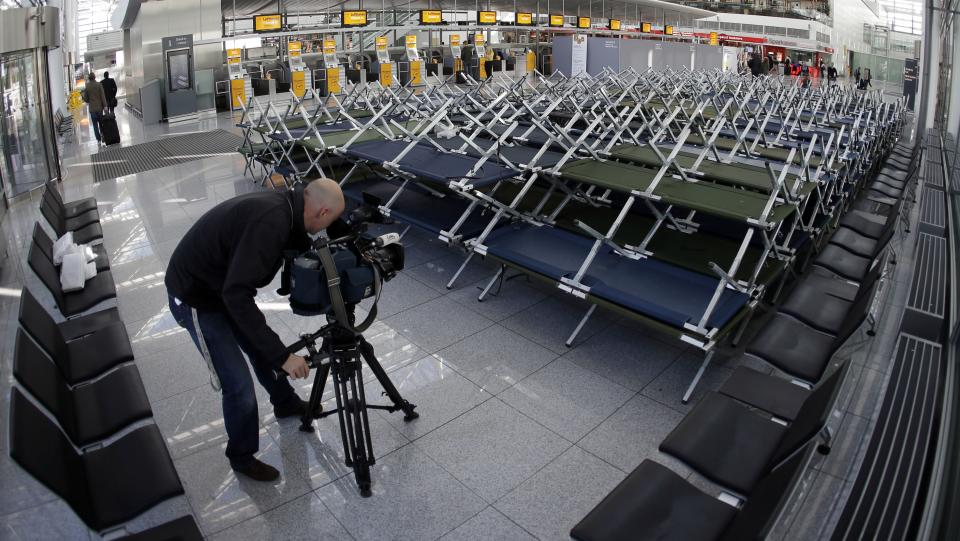A camera man films beds for stranded passengers as flight attendants of German Lufthansa airline went on a 24-hour-strike for higher wages at the airport in Munich, southern Germany, on Friday, Sept. 7, 2012. (AP Photo/Matthias Schrader)