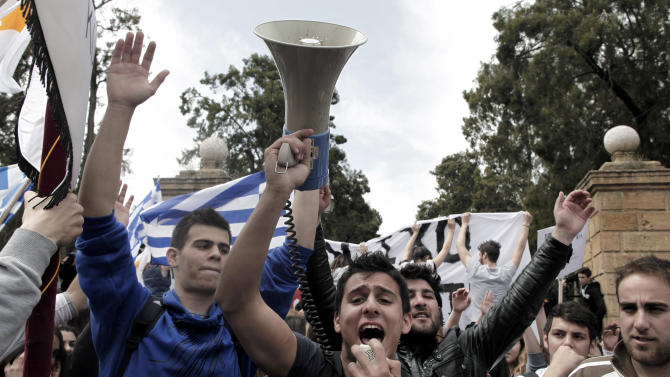 Cypriot students protest against the bailout package outside the Presidential Palace, in capital Nicosia, on Tuesday, March 26, 2013. Banks across Cyprus remain firmly padlocked Tuesday after financial authorities extended the country's bank closure, fearing worried depositors will rush to drain their accounts. The shut-down is hammering businesses, which have been without access to their funds for more than a week.(AP Photo/Petros Giannakouris)