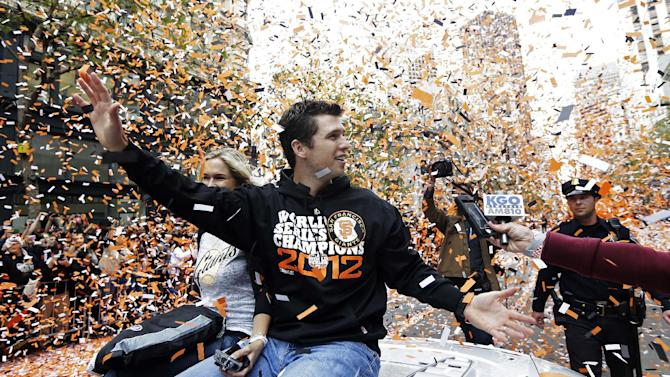 FILE - In this Oct. 31, 2012, file photo, San Francisco Giants catcher Buster Posey waves and is showered with confetti during their victory parade for winning baseball's World Series on Market Street in San Francisco. Posey is the favorite to win National League Most Valuable Player, to be announced Thursday, Nov. 15, 2012.  (AP Photo/Marcio J. Sanchez, File)