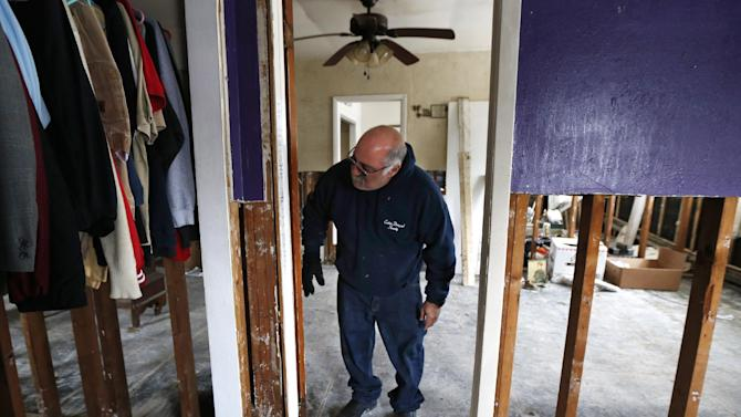 "FILE - In this file photo of Jan. 23, 2013, Anthony Cavallo looks at the doorway to the room of his daughter Amy in Union Beach, N.J., where the family has been living in a trailer next to their home damaged by Superstorm Sandy because the house was uninhabitable as they awaited storm aid. Last week they finally received a check in the mail, marked ""full and final payment,"" for $104,000. Cavallo said that is less than his policy limit, and less than half of what it will cost to rebuild. (AP Photo/Julio Cortez, file)"