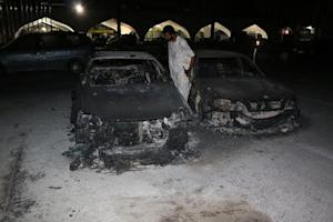 A member of the Zintan city forces inspects burnt cars after a rival militia shelled Tripoli International Airport in Tripoli