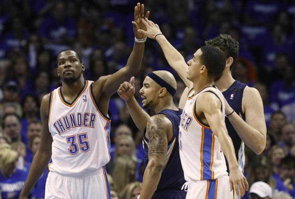 Oklahoma City Thunder forward Kevin Durant (35) hi fives teammate Kevin Martin (23) over the top of Memphis Grizzlies guard Jerryd Bayless (7) during the second quarter of Game 1 of their Western Conference Semifinals NBA basketball playoff series in Oklahoma City, Sunday, May 5, 2013. (AP Photo/Sue Ogrocki)