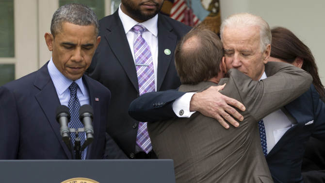 President Barack Obama stands at the podium at left as Mark Barden, the father of Newtown shooting victim Daniel is embraced by Vice President Joe Biden during a news conference in the Rose Garden of the White House, Wednesday, April 17, 2013, in Washington, about measures to reduce gun violence. (AP Photo/Carolyn Kaster)