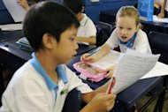 Happy Rogers (R), the daughter of US investor Jim Rogers, discusses her Mandarin examination paper with her classmate at Nanyang Primary School in Singapore in 2011. As far back as 25 years ago, Rogers already believed China would be the next economic superpower and young people the world over should prepare for the future by learning Mandarin