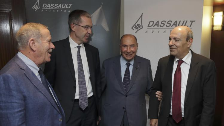 Eric Trappier, Dassault Aviation Chairman and CEO, speaks with Serge Dassault, French UMP political party member and CEO of Groupe Dassault Holding, after the company's 2014 First-Half results presentation in Saint Cloud near Paris