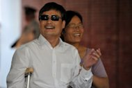 Blind Chinese activist Chen Guangcheng ( L) and his wife Yuan Weijing smile upon their arrival at the New York University Village appartment complex in Manhattan in New York, May 19, 2012. Chinese and American diplomats scrambled to find a solution after Chen sought refuge at the US embassy in Beijing