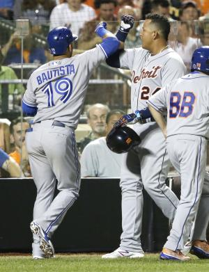American League's Miguel Cabrera, of the Detroit Tigers, is congratulated by American League's Jose Bautista (19), of the Toronto Blue Jays, after scoring on Bautista's sacrifice fly during the fourth inning of the MLB All-Star baseball game, on Tuesday, July 16, 2013, in New York.(AP Photo/Matt Slocum)