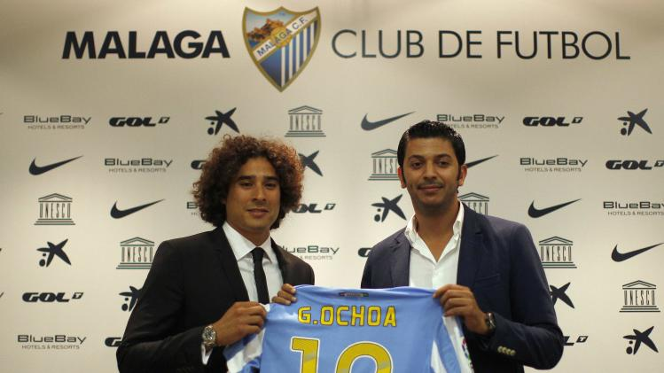 Malaga's newly signed goalkeeper Guillermo Ochoa from Mexico and Malaga's vice-president Shatat hold a Malaga team shirt during Ochoa's official presentation at the Rosaleda stadium, in Malaga