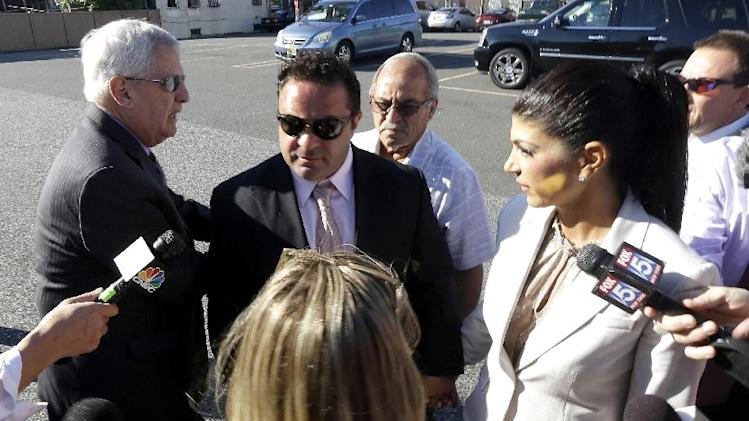 "Teresa Giudice, 41, right, and her husband Giuseppe ""Joe"" Giudice, 43, center, of Montville Township, N.J., walk toward Martin Luther King, Jr. Courthouse before a court appearance, Tuesday, July 30, 2013, in Newark, N.J. The two stars of the ""Real Housewives of New Jersey"" were indicted Monday on federal fraud charges, accused of exaggerating their income while applying for loans before their TV show debuted in 2009, then hiding their improving fortunes in a bankruptcy filing after their first season aired. They are charged in a 39-count indictment with conspiracy to commit mail and wire fraud, bank fraud, making false statements on loan applications and bankruptcy fraud. (AP Photo/Julio Cortez)"