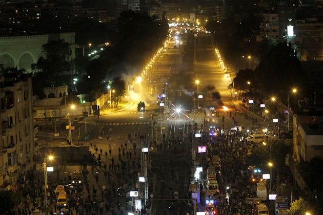 Egyptian protesters shoot fireworks towards anti-riot policemen as they fire tear gas during clashes in front of the presidential palace in Cairo, Egypt, Friday, Feb. 1, 2013. Thousands of protesters