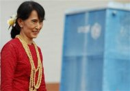 Aung San Suu Kyi smiles as she visits a polling station in Kawhmu township