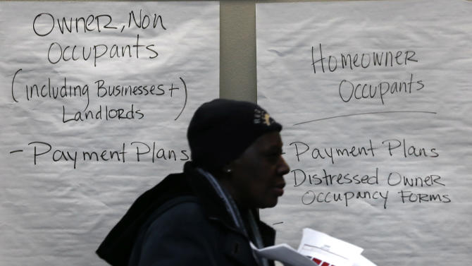 A homeowner carries paperwork to a conference room in Detroit's Cobo Center for cases being heard to avoid foreclosure from tax debts in Detroit Thursday, Jan. 29, 2015. Hundreds of Detroit homeowners at risk of losing their property are flocking to hearings that offer them a last-ditch chance to avoid foreclosure from tax debts. (AP Photo/Paul Sancya)
