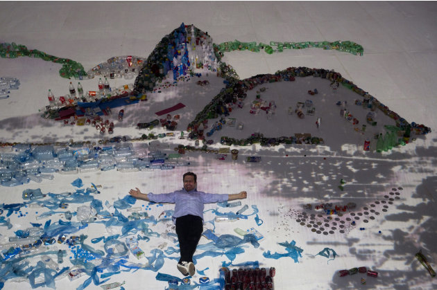 "Brazilian artist Vik Muniz poses for a photo as he lies on his ""Landscape"" project that uses waste to recreate the image of Guanabara Bay in Rio de Janeiro, Brazil, Saturday, June 16, 2012. Muniz's pr"