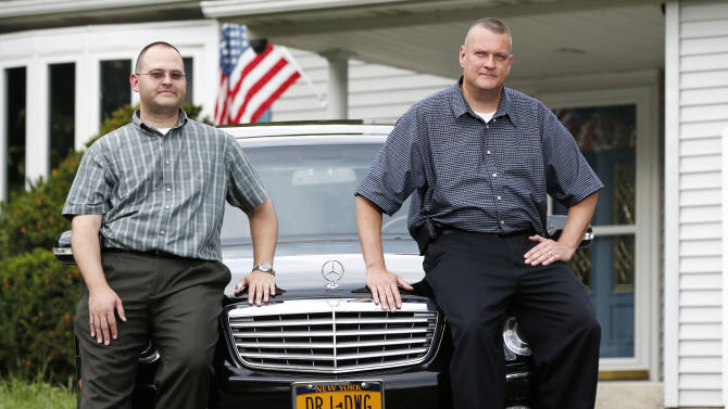 In this Tuesday, July 17, 2012 photo, Donald Grandchamp, left, and David Janulis, who were married last year in Albany, N.Y., pose in their driveway at their home in Glenmont, N.Y. Their initials are on the license plate. New York lawmakers approved the gay marriage measure after weeks of intensive lobbying and maneuvering by Gov. Andrew Cuomo. The vote was a nail biter, with four Republican state senators whose support made way for its passage revealing their positions at the last moment. Late on the night of June 24, 2011, a Friday, New York became the sixth and largest state to sanction gay marriage, more than doubling the number of Americans living with a same-sex marriage law. The New York law took effect a month later with a whirlwind of weddings that started in the minutes after midnight. (AP Photo/Mike Groll)