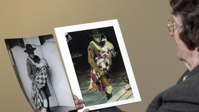 """Mary Immen Hall of Bennington, Vt., looks at the1940 Norman Rockwell illustration """"A Scout is Helpful"""" and the photograph it was created from at the Bennington Museum on Friday, Sept. 28, 2012, in Bennington, Vt. Hall modeled as the little girl in the illustration. (AP Photo/Mike Groll)"""