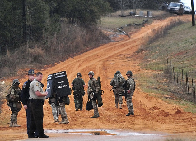 Law enforcement personnel work at check point Wednesday, Jan. 30, 2013, in Midland City, Ala., near the home  where the Tuesday's school bus shooting suspect is barricaded in a bunker with a young chi