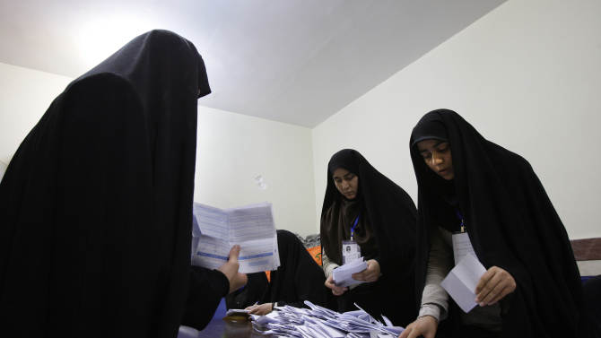 Iranian electoral workers count the ballots of the parliamentary runoff elections, in a polling station, in Tehran, Iran, Friday, May 4, 2012. 130 hopefuls competed for 65 seats in 33 constituencies including the capital Tehran with 25 undecided seats. Conservative opponents of President Mahmoud Ahmadinejad have already won majority of seats of the new parliament in the first round of the elections in March. (AP Photo/Vahid Salemi)