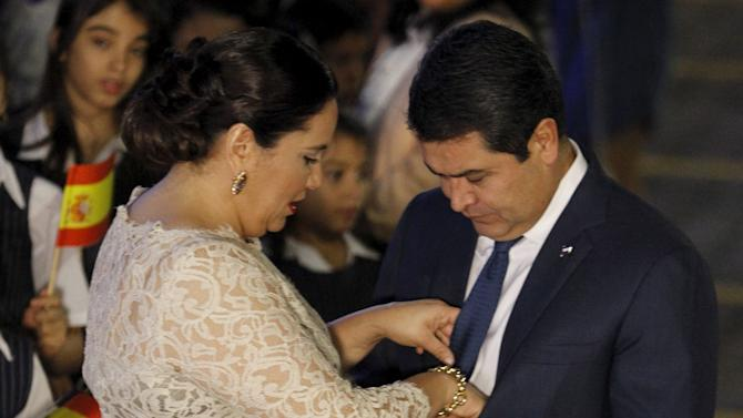Honduras' President Juan Orlando Hernandez has his tie straightened by his wife Ana Garcia while waiting for the arrival of Spain's Queen Letizia for a gala dinner at presidential palace in Tegucigalpa