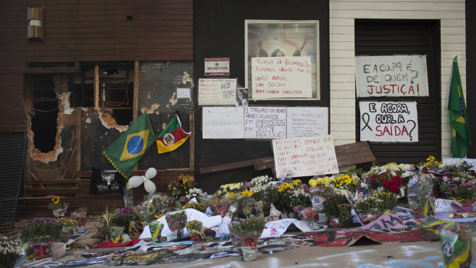 Posters, flowers, balloons and flags make up part of a makeshift memorial outside the Kiss nightclub in Santa Maria, Brazil, Wednesday, Jan. 30, 2013. A fast-moving fire roared through the crowded, windowless nightclub in this southern Brazilian city early Sunday, killing more than 230 people. Most of the dead were college students 18 to 21 years old, but they also included some minors. Almost all died from smoke inhalation rather than burns. The blaze was the deadliest in Brazil since at least 1961, when a fire that swept through a circus killed 503 people in Niteroi, Rio de Janeiro. (AP Photo/Felipe Dana)