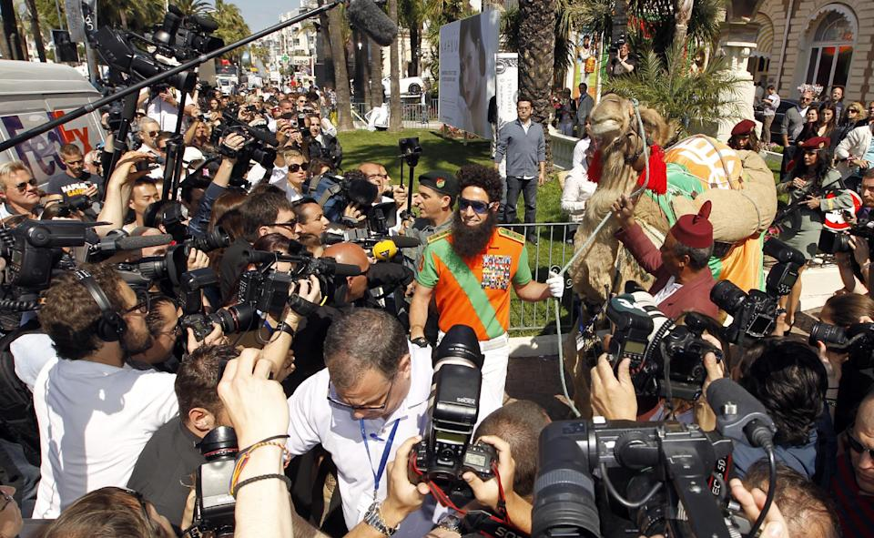 Actor Sacha Baron Cohen, center, poses with a camel during a photo call for The Dictator at the 65th international film festival, in Cannes, southern France, Wednesday, May 16, 2012. (AP Photo/Joel Ryan)