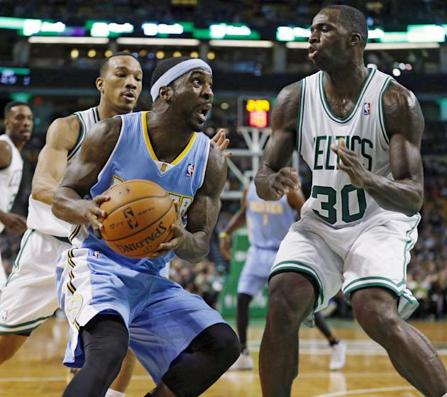 Denver Nuggets' Ty Lawson, center, drives for the basket as Boston Celtics' Brandon Bass (30) defends in the second quarter of an NBA basketball game in Boston, Friday, Dec. 6, 2013