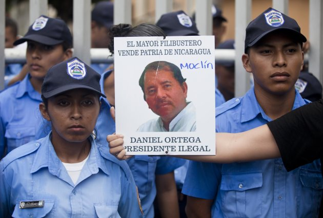 "<p> A demonstrator holds out a picture of Nicaragua's President Daniel Ortega that reads in Spanish ""The biggest thief and traitor of Nicaragua, Daniel Ortega illegal President"" in front of a line of police during a protest against a canal project outside the National Assembly in Managua, Nicaragua, Thursday, June 13, 2013. A multi-billion dollar proposal to plow a massive rival to the Panama Canal across the middle of Nicaragua was approved by the National Assembly Thursday, capping a lightning-fast approval process that has provoked deep skepticism among shipping experts and concern among environmentalists. (AP Photo/Esteban Felix)"