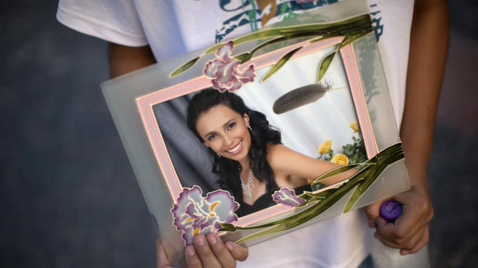 A youth holds a photograph of his sister Pamella Lopes, who died in a nightclub fire, in a public square near the club in Santa Maria, Brazil, Monday, Jan. 28, 2013. A fast-moving fire roared through the crowded, windowless Kiss nightclub in this southern Brazilian city early Sunday, killing more than 230 people. Many of the victims were under 20 years old, including some minors. (AP Photo/Felipe Dana)
