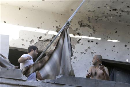 Two men inspect their damage house after two rockets hit their area in a Beirut suburbs