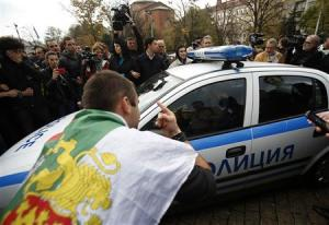 Protesters try to block a police vehicle during a demonstration near the parliament in central Sofia