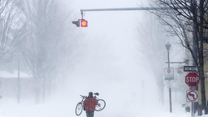 Juan Tavares carries his bike rather than risk riding on a snow-covered street during a blizzard, Saturday, Feb. 9, 2013, in Portland, Maine. The storm dumped more than 30 inches of snow as of Saturday afternoon, breaking the record for the biggest storm on record. (AP Photo/Robert F. Bukaty)