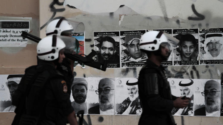 Bahraini riot policemen look for anti-government protesters during clashes in Sitra, Bahrain, Monday, Sept. 3, 2012. Pictures of people killed in the unrest and of jailed political leaders are plastered on the wall. Verdicts are expected Tuesday for numerous jailed leaders, medical workers and activists. (AP Photo/Hasan Jamali)