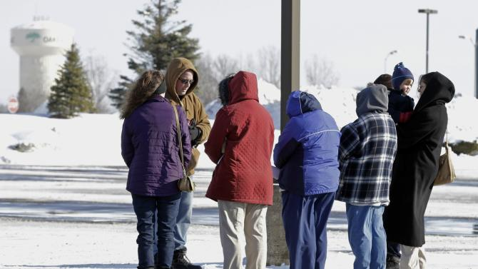 Pastor Chris Duckworth, facing group, of Grace Lutheran Church of St. Paul, Minn., leads a small group in prayer, song and scripture in the parking lot of a Rainbow Foods store Tuesday, Feb. 12, 2013 in Oakdale, Minn., following an apparent random shooting at passing vehicles Monday night near the store that left a 9-year-old boy dead and his mother and another woman wounded. The victims in the two vehicles sped to the food store for help. A 34-year-old Oakdale man is in custody. (AP Photo/Jim Mone)
