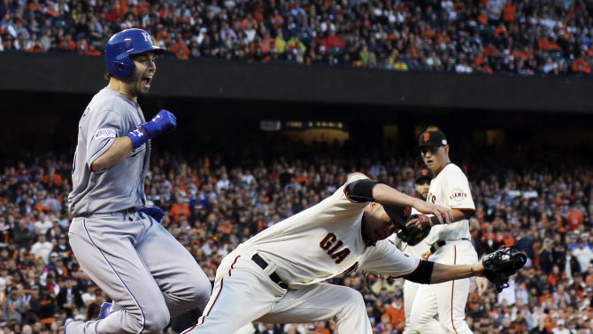 Kansas City Royals' Eric Hosmer is tripped as he beats a throw to first with San Francisco Giants' Ryan Vogelsong covering during the third inning of Game 4 of baseball's World Series Saturday, Oct. 25, 2014, in San Francisco. (AP Photo/David J. Phillip)