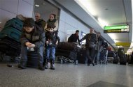 Children sit on luggage and wait in line as they wait for information about their delayed flight at La Guardia airport in New York January 6, 2014. REUTERS/Carlo Allegri