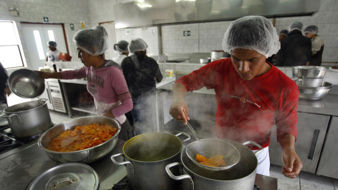 In this photo taken Dec. 18, 2010, students prepare food at the cooking school at Pachacutec vocational institute in Lima, Peru. The school is a 3-year-old cooking school founded for poor students by culinary maestro Gaston Acurio.   (AP Photo/Karel Navarro)