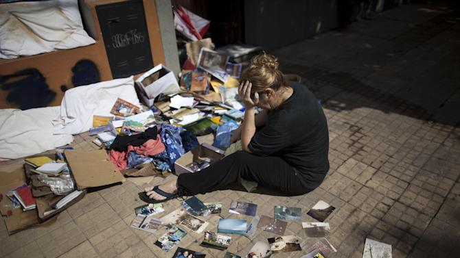 Vilma Gorostiaga cries outside her home as she dries her family pictures on the ground in La Plata, in Argentina's Buenos Aires province, Thursday, April 4, 2013. Buenos Aires Gov. Daniel Scioli says 49 people died in this flooded capital of Argentina's largest province as torrential rains swamped entire neighborhoods, washing away cars and flooding some houses to their rooftops. (AP Photo/Natacha Pisarenko)