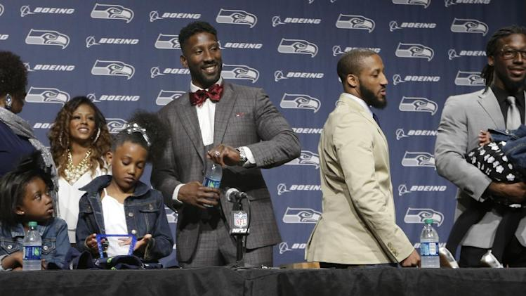 Seattle Seahawks' Marcus Trufant, center, smiles as he stands with family members following a news conference announcing his retirement from football after signing with the team a day earlier, Thursday, April 24, 2014, in Renton, Wash. Trufant started 125 games in a Seattle career that lasted from 2003 to 2012. The cornerback was a first-round pick in 2003 out of Washington State and immediately moved into the starting lineup, playing a key role on the 2005 team that advanced to the franchise's first Super Bowl