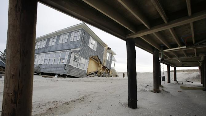 A raised home with modest damage is seen near a severely damaged beach front home in Mantoloking, N.J., Friday, Feb. 22, 2013. One of the hardest-hit Jersey shore communities, Mantoloking, will allow its residents to begin moving back home Friday. It is the last shore town to do so. It's not a mad rush. The winter population of the barrier island community totals only about 100 and many homes are not yet livable. (AP Photo/Mel Evans)