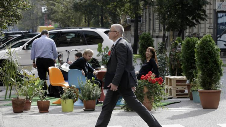 A man crosses a street past people participating in a PARK(ing) Day event in Riga