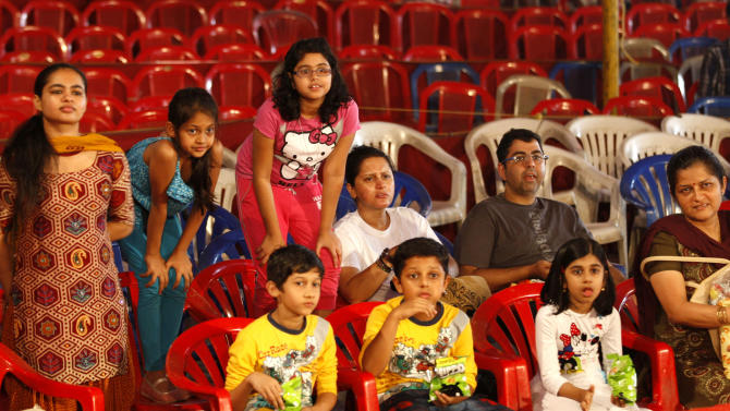 In this April 11, 2013 photo, Indian spectators watch a performance at the Rambo Circus on the outskirts of Mumbai, India. Circuses around the world may struggle to compete with an ever-increasing array of entertainment options, but India's once-widespread industry in particular has gone through cataclysmic changes. In the 1990s, there were 300 circuses operating throughout the country. That number has now dwindled to about 30, says circus manager John Matthew, and many of those are in financial trouble due to rising costs of renting field space, shrinking revenues and - crucially - two Supreme Court rulings that took away two of the industry's main attractions. (AP Photo/Rafiq Maqbool)