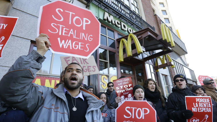 Demonstrator Zev Nicholson, of Boston, left, holds a placard and chants during a protest outside a McDonalds fast foot restaurant, Tuesday, March 18, 2014, in Boston, held to call attention to the denial of overtime pay and other violations protesters say deprive workers of the money they're owed. (AP Photo/Steven Senne)
