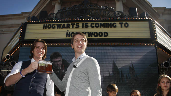 Harry Potter cast members James Phelps, left, and Oliver Phelps make a butterbeer toast as Universal Parks & Resorts announces the Harry Potter attraction is coming to Universal Studios Hollywood in Universal City, Calif., Tuesday, Dec. 6, 2011. The attraction opened in Orlando, Fla. last summer has been a big hit. (AP Photo/Jason Redmond)